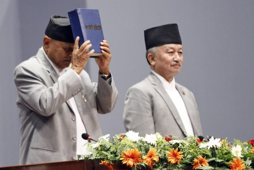 Nepalese President displaying the constitution which was formally adopted at the constitution Assemble hall in Kathmandu, Nepal, Sunday, Sep 20, 2015. (AP Photo/Niranjan Shrestha)